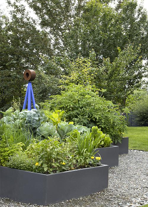 raised garden beds with blue sculpture