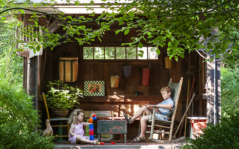 children playing in a wood playhouse with trees and greenery surrounding it